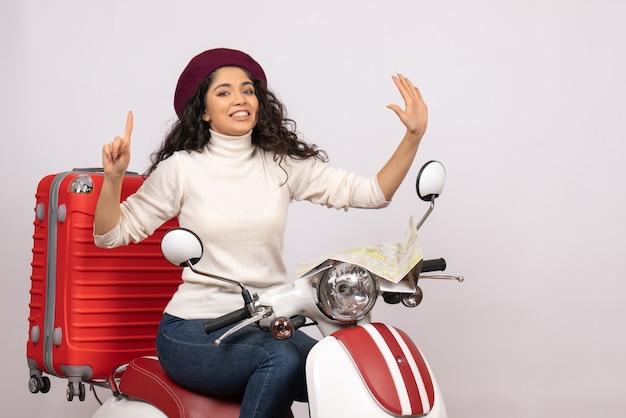 Vista frontal mujer joven sentada en bicicleta sobre fondo blanco color carretera motocicleta vehículo vacaciones mujer ciudad