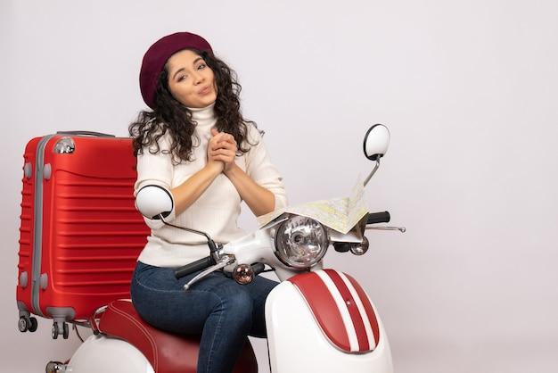 Vista frontal mujer joven sentada en bicicleta sobre el fondo blanco mujer vehículo de vacaciones motocicleta ciudad carretera color