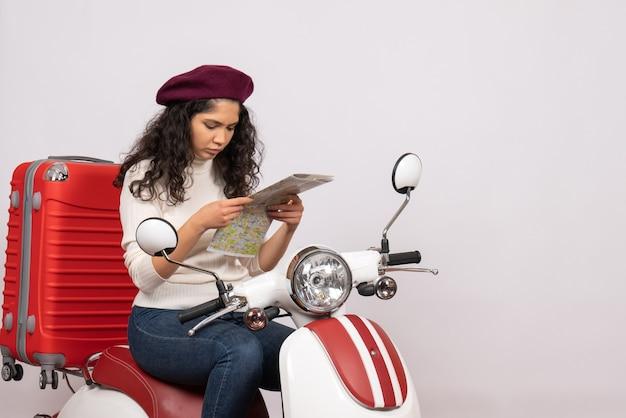 Vista frontal mujer joven sentada en bicicleta sosteniendo mapa de la ciudad sobre fondo blanco mujer vehículo de vacaciones motocicleta color de la carretera de la ciudad