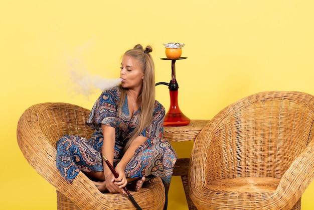 Vista frontal de la mujer joven sentada y fumando narguile en la pared amarilla