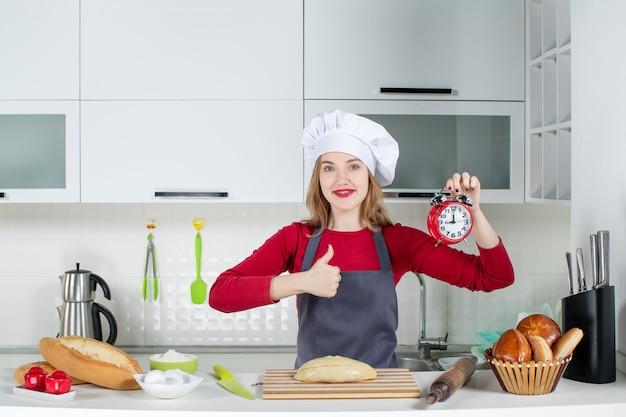Vista frontal de la mujer joven con sombrero de cocinero y delantal con reloj despertador rojo dando pulgar hacia arriba en la cocina
