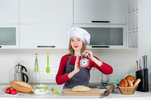 Vista frontal de la mujer joven con sombrero de cocinero y delantal sosteniendo el despertador rojo en la cocina