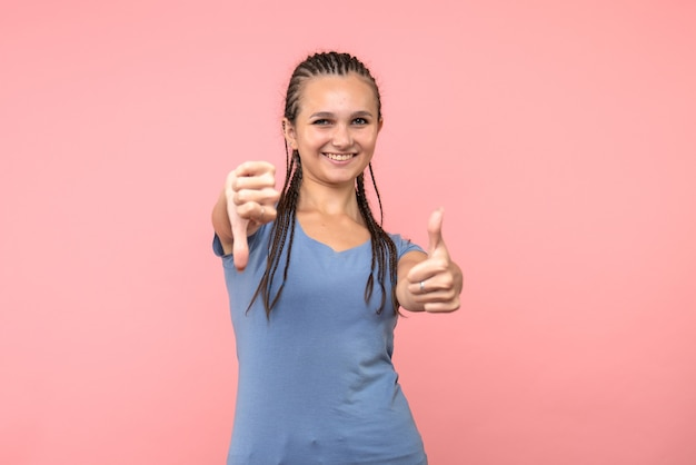 Vista frontal de la mujer joven sonriendo en rosa