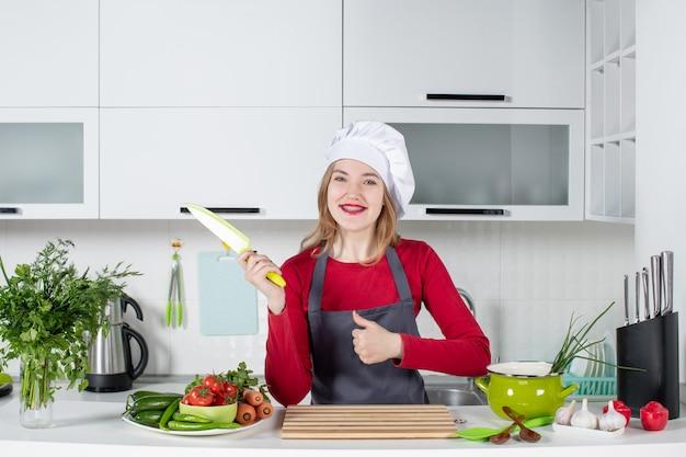 Vista frontal mujer joven sonriente en delantal sosteniendo un cuchillo dando pulgares hacia arriba