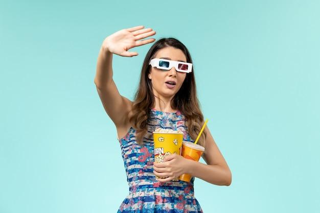 Vista frontal mujer joven sosteniendo bebida de palomitas de maíz en gafas de sol d sobre superficie azul claro