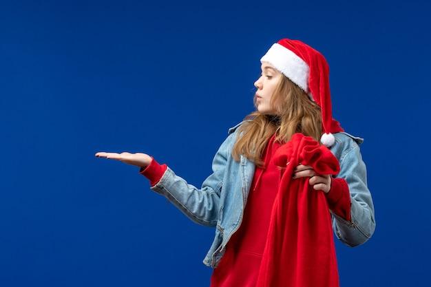 Vista frontal mujer joven sosteniendo la bolsa con regalos sobre fondo azul vacaciones emociones navideñas