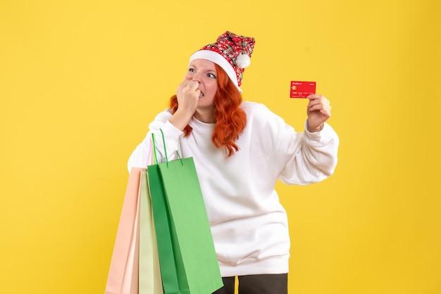 Vista frontal de la mujer joven sosteniendo bolsas de la compra y tarjeta bancaria en la pared amarilla
