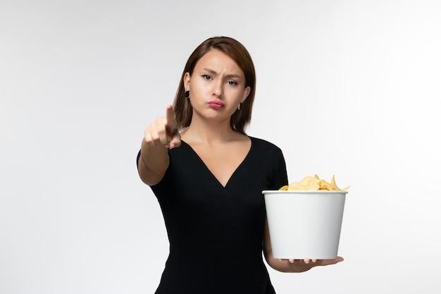 Vista frontal mujer joven sosteniendo la cesta con papas fritas viendo la película sobre una superficie blanca