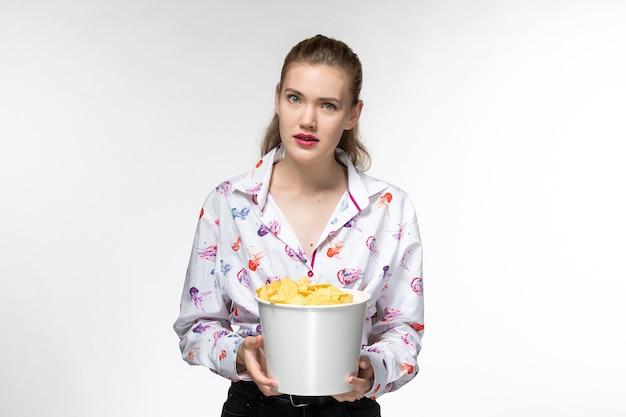 Vista frontal mujer joven sosteniendo la cesta con papas fritas viendo la película en la superficie blanca clara