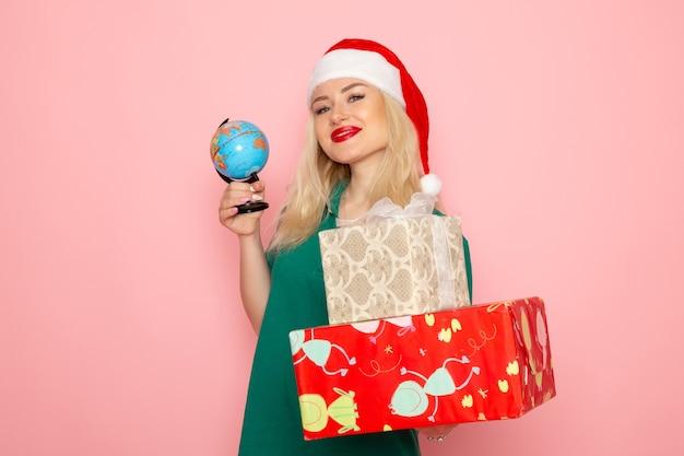 Vista frontal mujer joven sosteniendo globo y regalos de navidad en la pared rosa foto mujer navidad año nuevo color vacaciones