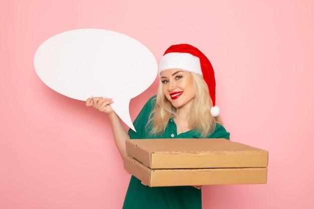 Vista frontal mujer joven sosteniendo un gran cartel blanco y cajas de comida en una pared rosa trabajo fotográfico uniforme de mensajería de trabajo de vacaciones de año nuevo