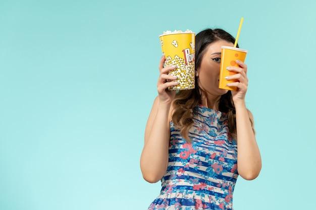Vista frontal mujer joven sosteniendo palomitas de maíz y bebida asustada de la película en superficie azul