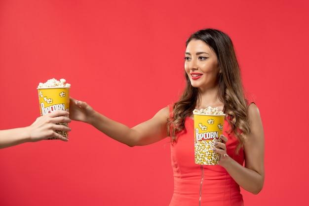 Vista frontal mujer joven sosteniendo paquetes de palomitas de maíz en el escritorio rojo