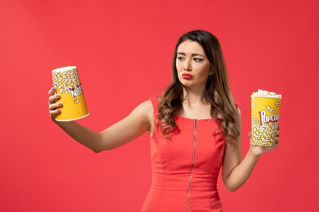 Vista frontal mujer joven sosteniendo paquetes de palomitas de maíz en la superficie roja