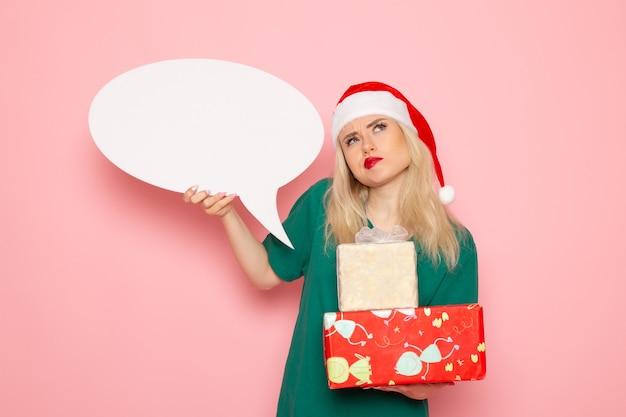 Vista frontal mujer joven sosteniendo regalos de navidad y letrero blanco en la pared rosa mujer regalo color nieve vacaciones de año nuevo