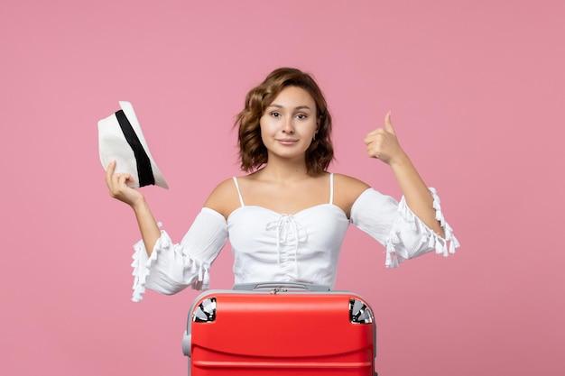 Vista frontal de la mujer joven sosteniendo el sombrero y preparándose para el viaje con bolsa roja en la pared de color rosa claro