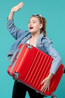 Vista frontal mujer joven sosteniendo su bolso rojo y preparándose para el viaje en el espacio azul claro