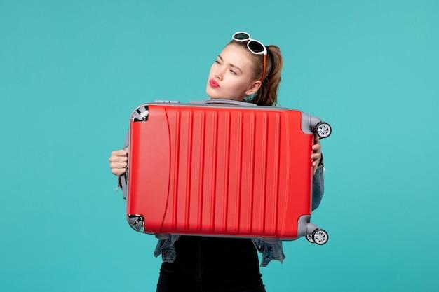 Vista frontal mujer joven sosteniendo su bolso rojo y preparándose para el viaje en el espacio azul