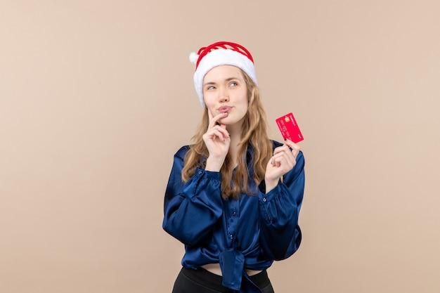 Vista frontal mujer joven sosteniendo una tarjeta bancaria roja sobre fondo rosa dinero vacaciones año nuevo navidad foto emoción lugar libre