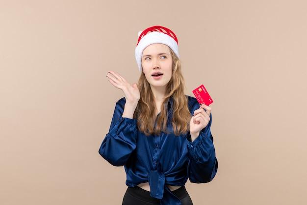 Vista frontal mujer joven sosteniendo una tarjeta bancaria roja sobre un fondo rosa foto de dinero vacaciones año nuevo emoción de navidad