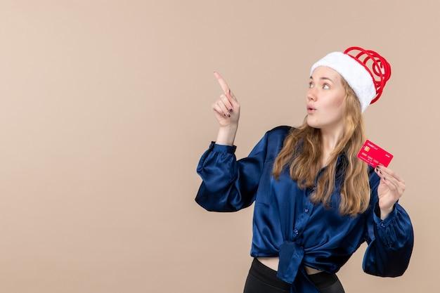 Vista frontal mujer joven sosteniendo una tarjeta bancaria roja sobre fondo rosa foto de vacaciones año nuevo dinero de navidad emoción espacio libre