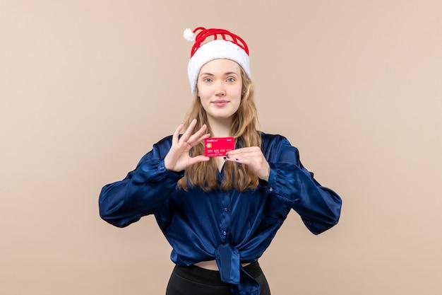 Vista frontal mujer joven sosteniendo una tarjeta bancaria roja sobre fondo rosa foto de vacaciones año nuevo emoción dinero de navidad
