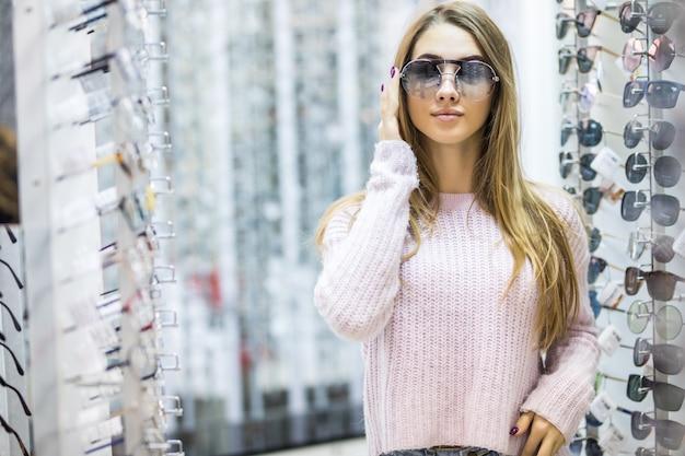 Vista frontal de la mujer joven en suéter blanco pruebe gafas en tienda profesional en