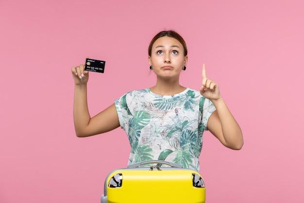 Vista frontal de la mujer joven con tarjeta bancaria negra en la pared rosa