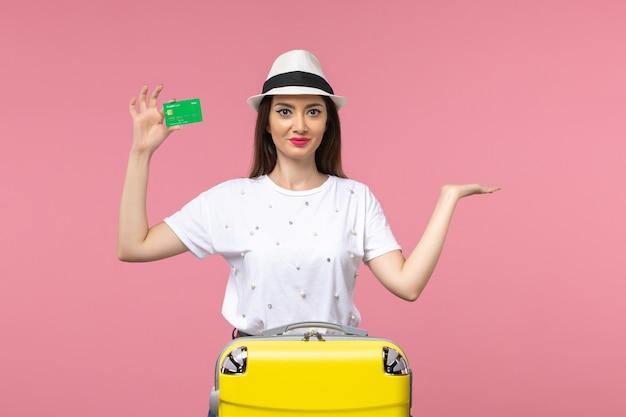 Vista frontal mujer joven con tarjeta bancaria en la pared rosa claro emoción mujer de viaje de verano