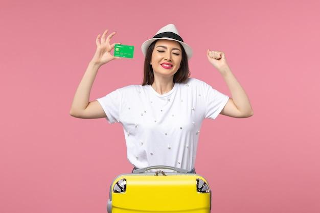 Vista frontal mujer joven con tarjeta bancaria en la pared rosa emoción mujer de viaje de verano