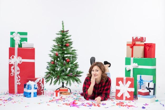 Vista frontal mujer joven tendido alrededor de regalos de navidad y árbol de vacaciones sobre fondo blanco regalo de año nuevo de navidad color nieve emociones
