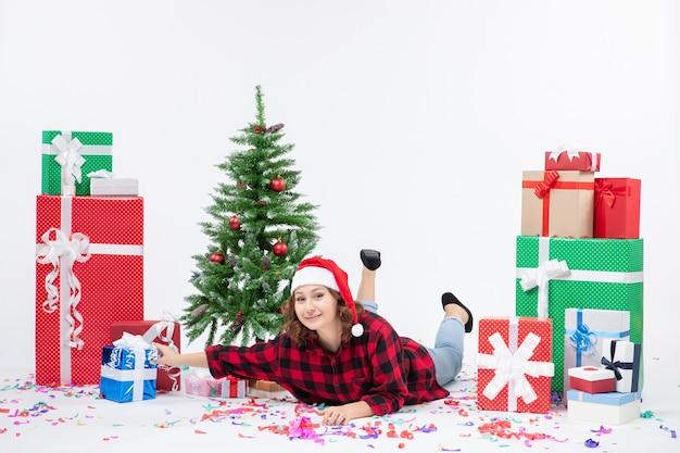 Vista frontal mujer joven tendido alrededor de regalos de navidad y arbolito de vacaciones sobre fondo blanco mujer fría navidad año nuevo nieve