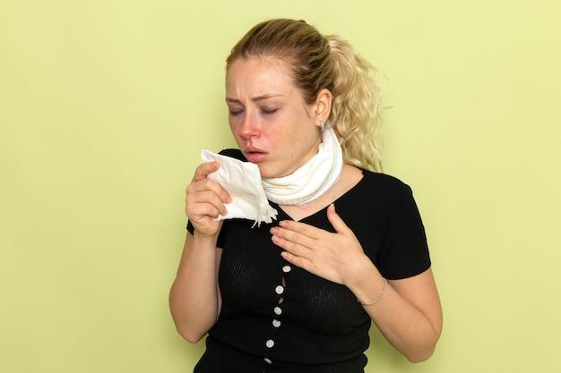 Vista frontal mujer joven con toalla blanca alrededor de su garganta sintiéndose muy enferma y enferma estornudando en la pared verde claro enfermedad enfermedad salud femenina niña