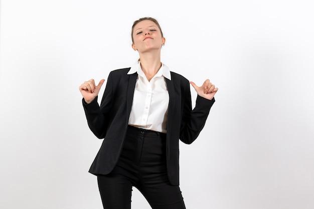 Vista frontal mujer joven en traje clásico estricto posando sobre el fondo blanco trabajo traje de negocios trabajo mujer mujer
