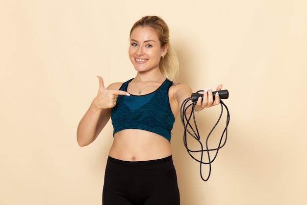 Vista frontal mujer joven en traje deportivo sosteniendo cuerdas para saltar en la pared blanca, salud, belleza, entrenamientos, salto, deporte corporal