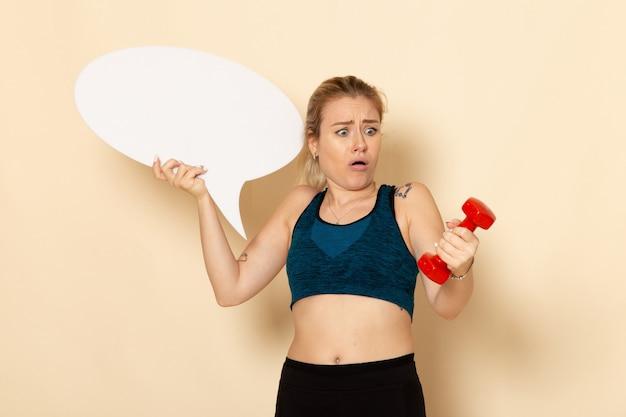 Vista frontal mujer joven en traje deportivo sosteniendo pesas y bocadillo de diálogo blanco