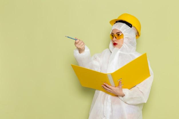 Vista frontal mujer joven en traje especial blanco y casco amarillo sosteniendo archivos amarillos en la ciencia uniforme del traje espacial verde