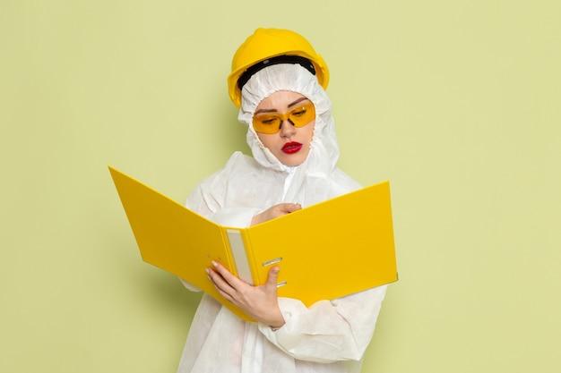 Vista frontal mujer joven en traje especial blanco y casco amarillo sosteniendo archivos amarillos y escribiendo en la ciencia uniforme del traje espacial verde