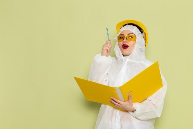 Vista frontal mujer joven en traje especial blanco y casco amarillo sosteniendo archivos amarillos y escribiendo en el espacio verde traje de trabajo de química ciencia uniforme