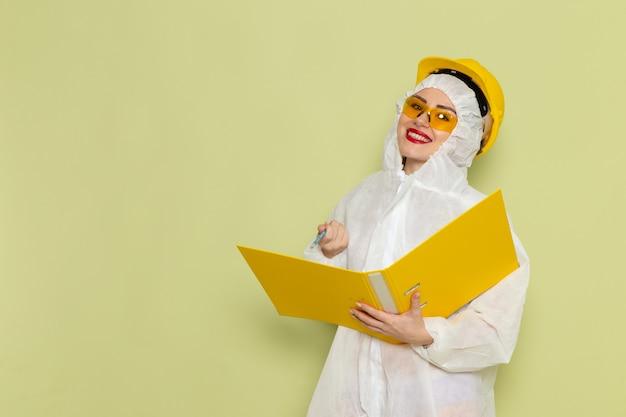 Vista frontal mujer joven en traje especial blanco y casco amarillo sosteniendo archivos amarillos sonriendo en la ciencia uniforme del traje espacial verde