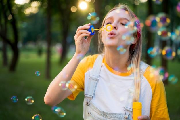 Vista frontal de la mujer jugando al aire libre con burbujas