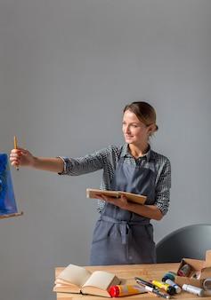 Vista frontal de la mujer con lápiz en delantal