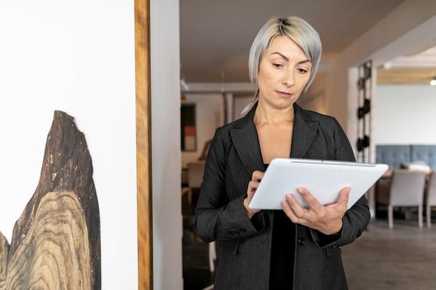 Vista frontal mujer leyendo de maqueta de tableta