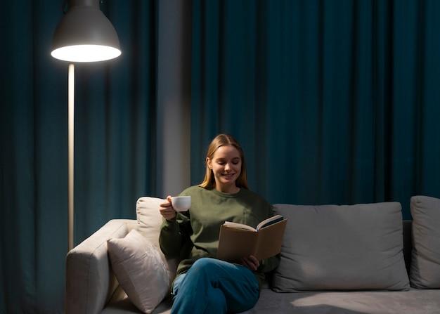 Vista frontal de la mujer leyendo en el sofá