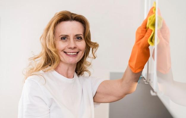 Vista frontal de la mujer limpiando los gabinetes de la cocina