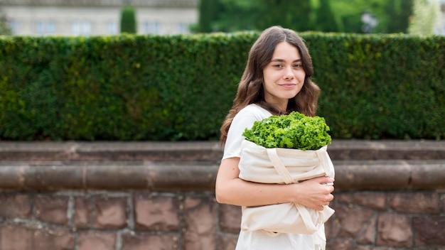 Vista frontal mujer llevando bolsa de comestibles