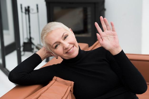 Vista frontal de la mujer madura feliz posando y saludando mientras sonríe
