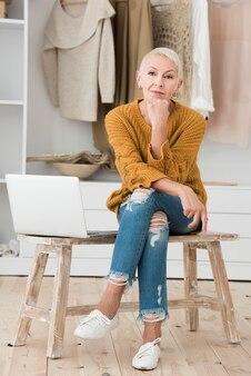 Vista frontal de la mujer madura posando con laptop en silla