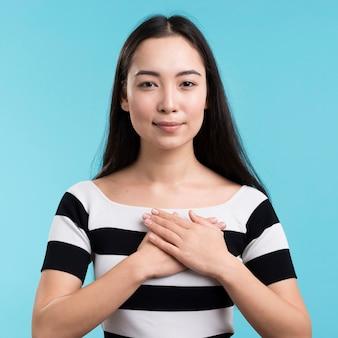 Vista frontal mujer con las manos en el corazón