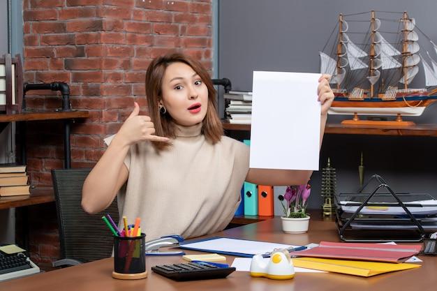 Vista frontal de la mujer maravillada haciendo llamarme señal de teléfono sentado en la oficina